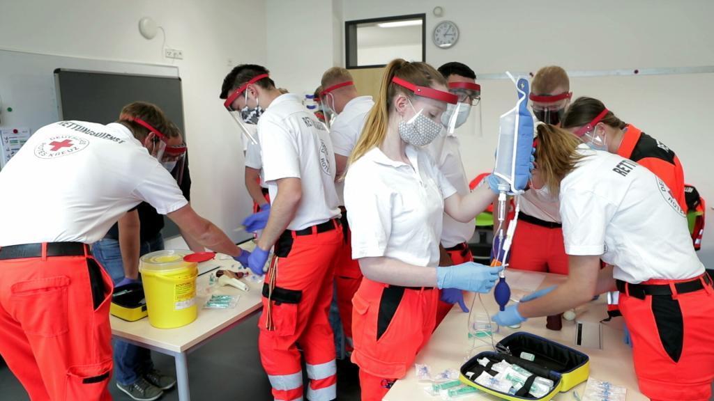 Rettungssanitäter im Unterricht mit geringem Abstand und Faceshield